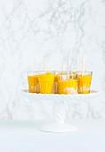Mango-Popsicles in Gläsern auf Porzellanständer vor Marmorhintergrund