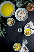 Golden Fennel Soba Noodle Soup is served with quick pickled veggies and white wine on a black wooden background