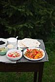 Hähnchen-Fajitas mit Tortillas, Pico de Gallo, Guacamole, schwarzen Bohnen, geriebenem Käse, Sauerrahm und Limette