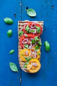Open sandwich, grilled baguette with yellow and red tomatoes, basil pesto and red onion