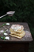 Waffles served with whipped cream, sprinkled icing sugar with cocoa powder