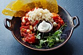 Tomato and bean stew with couscous and sour cream