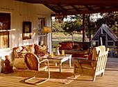 Sitzgruppe mit alten Möbeln auf der Veranda im gleißenden Sonnenlicht