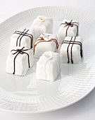 White petit fours decorated with chocolate icing and sugar flowers