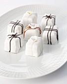 weiße Petit Fours mit Schokoglasur und Zuckerblüten verziert