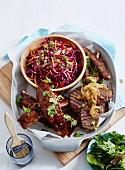 Grillplatte mit Rippchen, Steak und Würstchen serviert mit Coleslaw