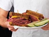 A man holding a plate of corned beef sandwiches
