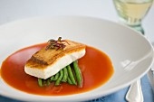 A halibut fillet with green beans in tomato consommé