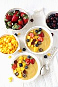 Healthy breakfast: mango and banana smoothie bowls topped with mango chunks, grapes, strawberries, and blueberries