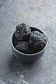 Three black truffles in a grey bowl