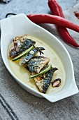 Fried sardines with garlic and lime in a serving bowl