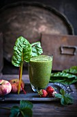 A green smoothie made of chard, strawberries and peaches