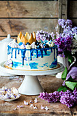 A birthday cake with blue-and-white decorations and a crown