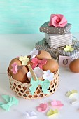 Blown eggs decorated with paper flowers and paper bows in Easter basket