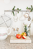 Apples and cutlery in glasses in front of kitchen utensils hanging from rod