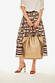 Frau in Midi-Rock mit Muster, goldfarbenem Leder-Shopper und Sandaletten mit Schnürung