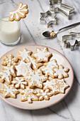 Butterplätzchen, weihnachtlich mit Zuckerglasur verziert, mit Milchglas und Ausstechförmchen