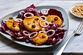 Wintery radicchio salad with oranges, red onions, raisins and pine nuts