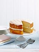 Vanillekuchen mit Cremefüllung und Icing, angeschnitten auf Kuchenständer