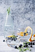 Tonic water cocktail with rosemary, blueberries and orange
