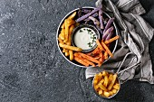 Variety of french fries traditional potatoes, purple potato, carrot served with white cheese sauce, salt, thyme in black bowl