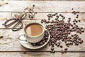 Milchkaffee in Tasse, Kaffeebohnen, Schere und Schnur