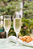Two glasses of Prosecco on a table outside with large cheese straws