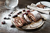 Chocolate swiss roll whole and chopped into slices with cherries and icing sugar