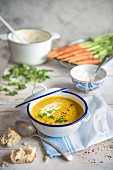 A bowl of carrot, corainder and coconut soup with bread