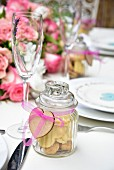 Heart shaped biscuits in a decorative gift jar on a festively laid table