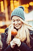 A young woman dressed for winter with a toffee apple at a Christmas market