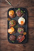Various burgers on a grill pan