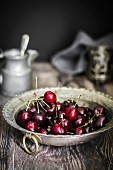 Freshly washed red summer cherries in a pewter bowl with jug