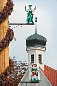A May pole with craftsmen figures on the church square of Weiler, Bavaria, Allgäu, Germany