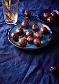 Round chocolate truffles on a blue plate