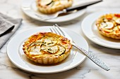 Puff pastry tarts with green and yellow zucchini and carrots