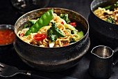 Asian noodles with kale, sugar snap peas, spring onions, and chili peppers