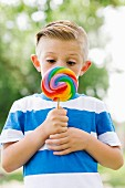 Boy squinting and holding big, colorful lollipop