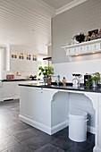 Große Landhausküche mit weißen Kassettenfronten und grauem Boden