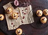 Cranberrymuffins auf Backpapier und Abkühlgitter (Aufsicht)