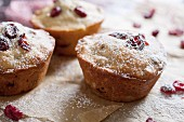 Freshly baked cranberry muffins on parchment paper with sugar icing