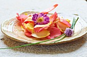 Delicate petals and chive blossoms on a plate