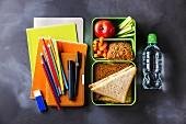 Sandwiches, Gemüse und Obst in Lunchbox, daneben Wasserflasche und Schulutensilien