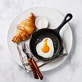 Breakfast with Fried egg on iron pan and croissant sandwich with cheese and ham on white plate on white background