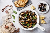 Mussels in cooking pan with parsley, toasted bread and fishnet on white background