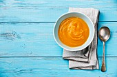 Pumpkin soup on blue wooden background