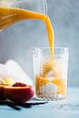 Pfirsich-Float (Getränk mit Eiscreme und Früchten) wird in Glas gegossen