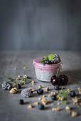Chiapudding mit Beeren und Kirschen im Glas vor grauem Hintergrund
