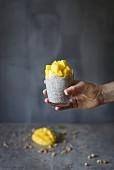 Chiapudding mit Mango im Glas vor grauem Hintergrund