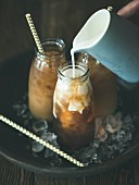 Cold Thai iced tea in glass bottles with milk pouring from jug on plate over dark wooden background